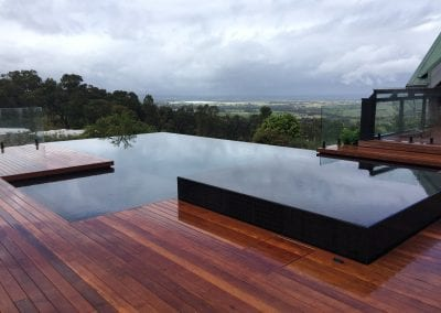 Luxury infinity pool surrounded by a hardwood deck